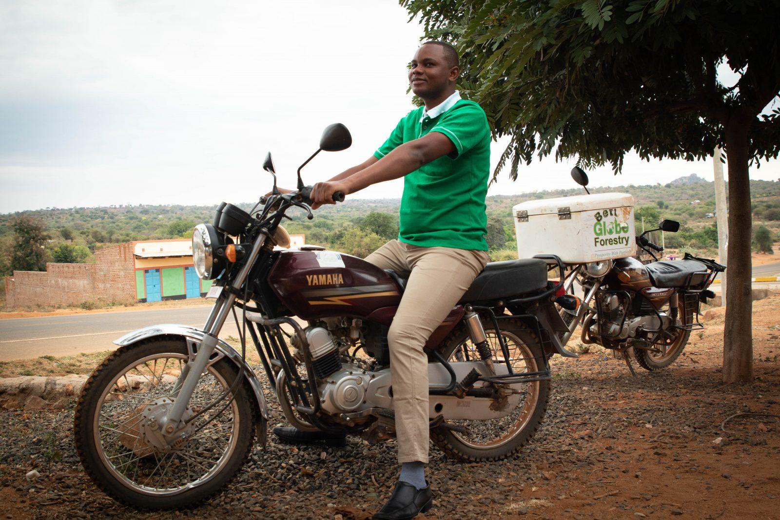Ambrose Musango, universitetsutbildad skogsmästare som är ansvarig för partnerbönderna i 7Forks-området på sin motorcykel.