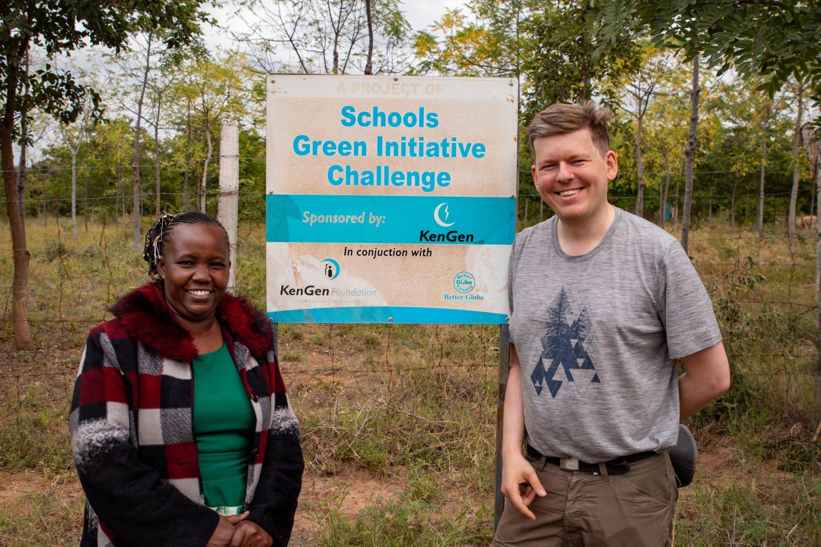 Rektorn på Kaewa Secondary School i Kindaruma tillsammans med mig framför skylten kring Green Initiative Challenge som är ett samarbete mellan KenGen, Better Globe och Bamburi.